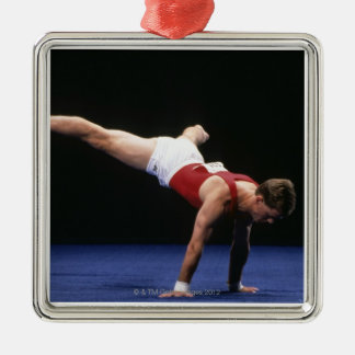 Male gymnast peforming a routine in the floor metal ornament