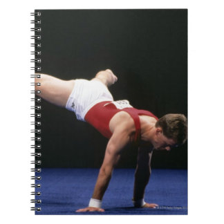 Male gymnast peforming a routine in the floor note book