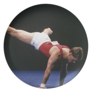 Male gymnast peforming a routine in the floor plates
