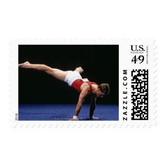 Male gymnast peforming a routine in the floor postage