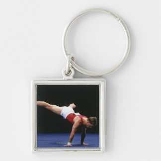 Male gymnast peforming a routine in the floor Silver-Colored square keychain