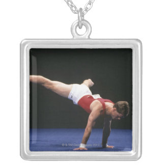 Male gymnast peforming a routine in the floor silver plated necklace