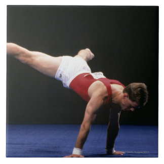 Male gymnast peforming a routine in the floor ceramic tiles