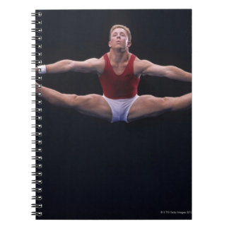 Male gymnast performing on the floor exercise notebook