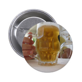Male hand holding a cold mug of light beer 2 inch round button