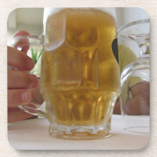 Male hand holding a cold mug of light beer drink coaster
