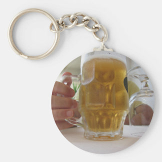 Male hand holding a cold mug of light beer keychain