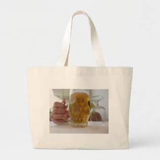 Male hand holding a cold mug of light beer large tote bag