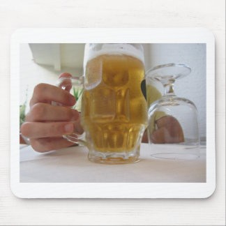 Male hand holding a cold mug of light beer mouse pad