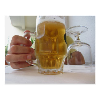 Male hand holding a cold mug of light beer postcard