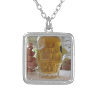 Male hand holding a cold mug of light beer silver plated necklace