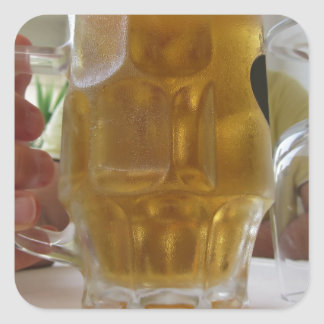 Male hand holding a cold mug of light beer square sticker