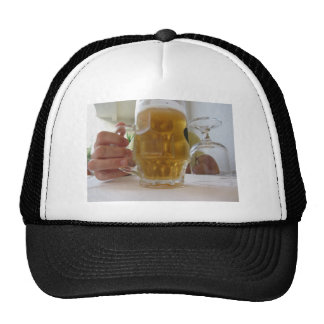 Male hand holding a cold mug of light beer trucker hat