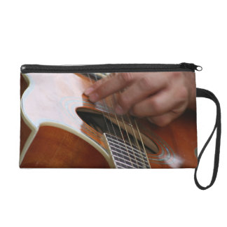 male hand holding pick on acoustic guitar wristlet clutch