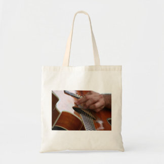 male hand holding pick on acoustic guitar bag