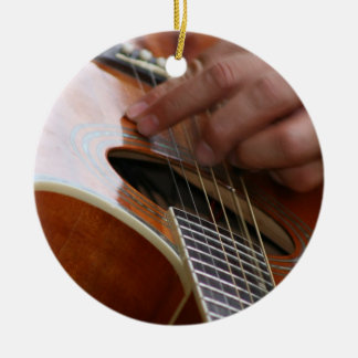 male hand holding pick on acoustic guitar christmas tree ornaments