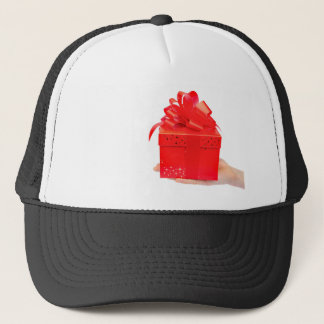 Male hand presenting red christmas box on hand trucker hat