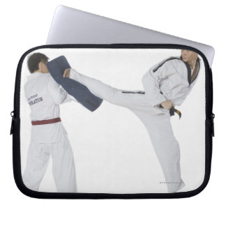 Male karate instructor teaching martial arts to 2 computer sleeves