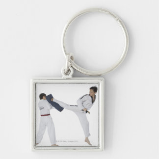 Male karate instructor teaching martial arts to 2 keychain