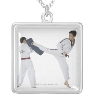 Male karate instructor teaching martial arts to 2 pendants