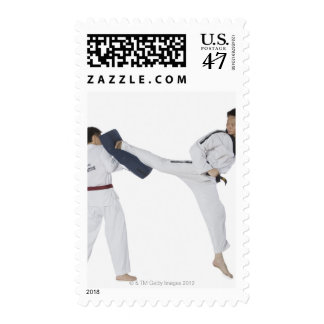 Male karate instructor teaching martial arts to 2 postage