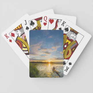 Male kayaker paddling sea kayak on still water deck of cards