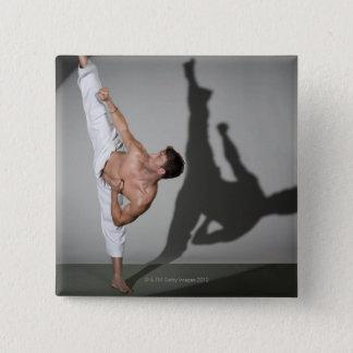 Male martial artist performing kick, studio shot button