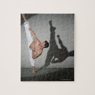 Male martial artist performing kick, studio shot jigsaw puzzle