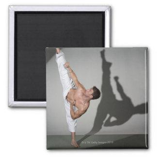 Male martial artist performing kick, studio shot refrigerator magnet