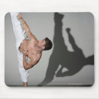 Male martial artist performing kick, studio shot mouse pad