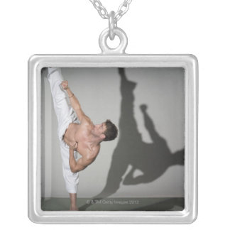 Male martial artist performing kick, studio shot silver plated necklace