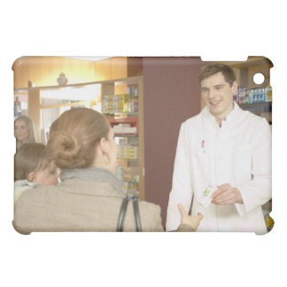 Male pharmacist handing medicine over to young cover for the iPad mini