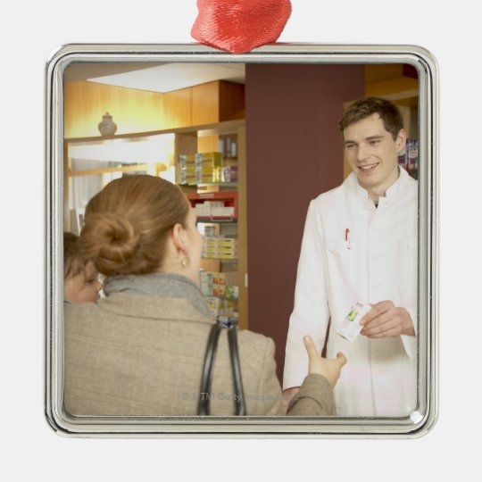 Male pharmacist handing medicine over to young metal ornament