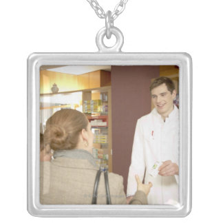 Male pharmacist handing medicine over to young square pendant necklace