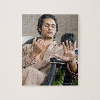 Man admiring his manicure jigsaw puzzle