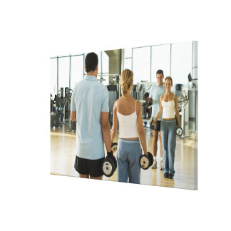 Man and woman lifting hand weights in front of a canvas print