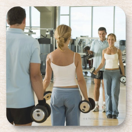 Man and woman lifting hand weights in front of a coaster