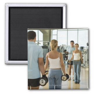 Man and woman lifting hand weights in front of a magnet