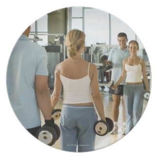 Man and woman lifting hand weights in front of a plates