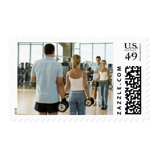 Man and woman lifting hand weights in front of a postage
