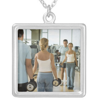 Man and woman lifting hand weights in front of a silver plated necklace