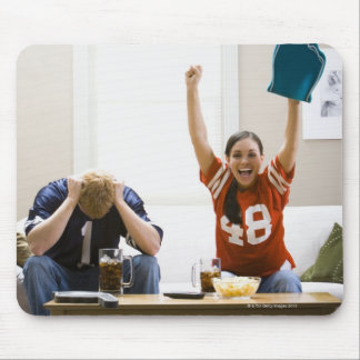 Man and woman sitting on sofa watching football mouse pad