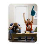 Man and woman sitting on sofa watching football rectangular magnets