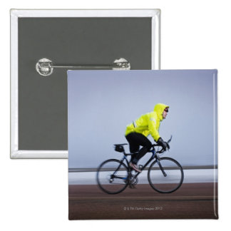 Man bicycles on a cold and foggy winter day. button