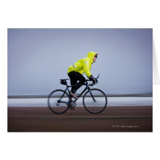 Man bicycles on a cold and foggy winter day. card
