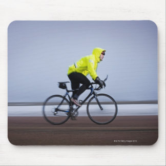 Man bicycles on a cold and foggy winter day. mouse pad