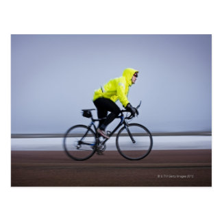 Man bicycles on a cold and foggy winter day. postcard