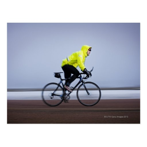 Man bicycles on a cold and foggy winter day. post card