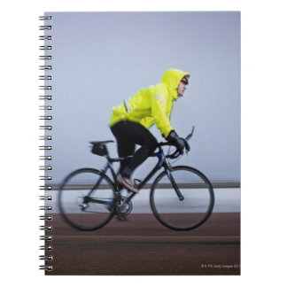 Man bicycles on a cold and foggy winter day. spiral notebook