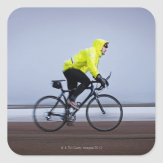 Man bicycles on a cold and foggy winter day. square sticker